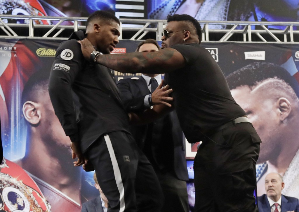 British boxer Anthony Joshua, left, is shoved by Jarrell Miller, right, as they pose for photographs during a news conference Tuesday, Feb. 19, 2019, ...