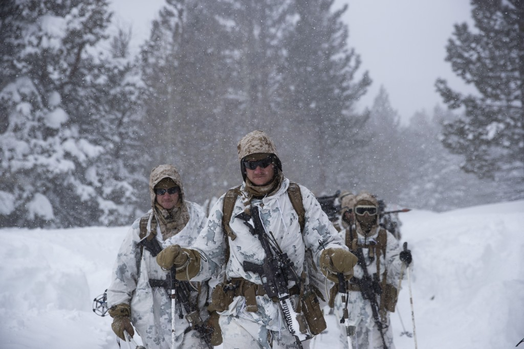 U.S. Marines walk along a snow-covered trail during their advanced cold-weather training at the Marine Corps Mountain Warfare Training Center Sunday, ...