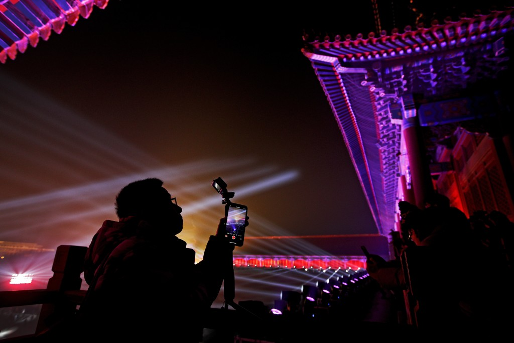 In this Tuesday, Feb. 19, 2019, photo, visitors take photos of the Forbidden City illuminated with lights for the Lantern Festival in Beijing. China l