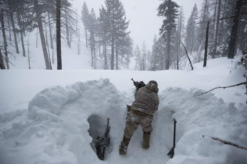 A U.S. Marine covers a machine gun in a trench while preparing for advanced cold-weather training at the Marine Corps Mountain Warfare Training Center...