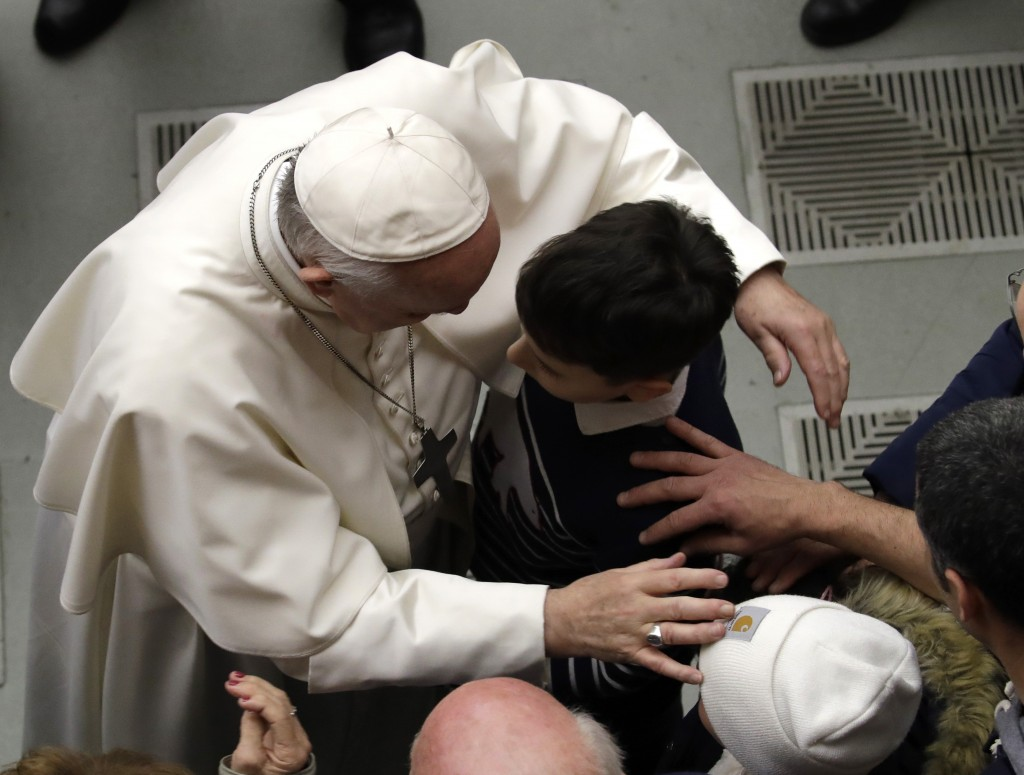 Pope Francis hugs a child as he poses for a photo at the end of his weekly general audience in the Paul VI Hall at the Vatican Wednesday, Feb. 20, 201