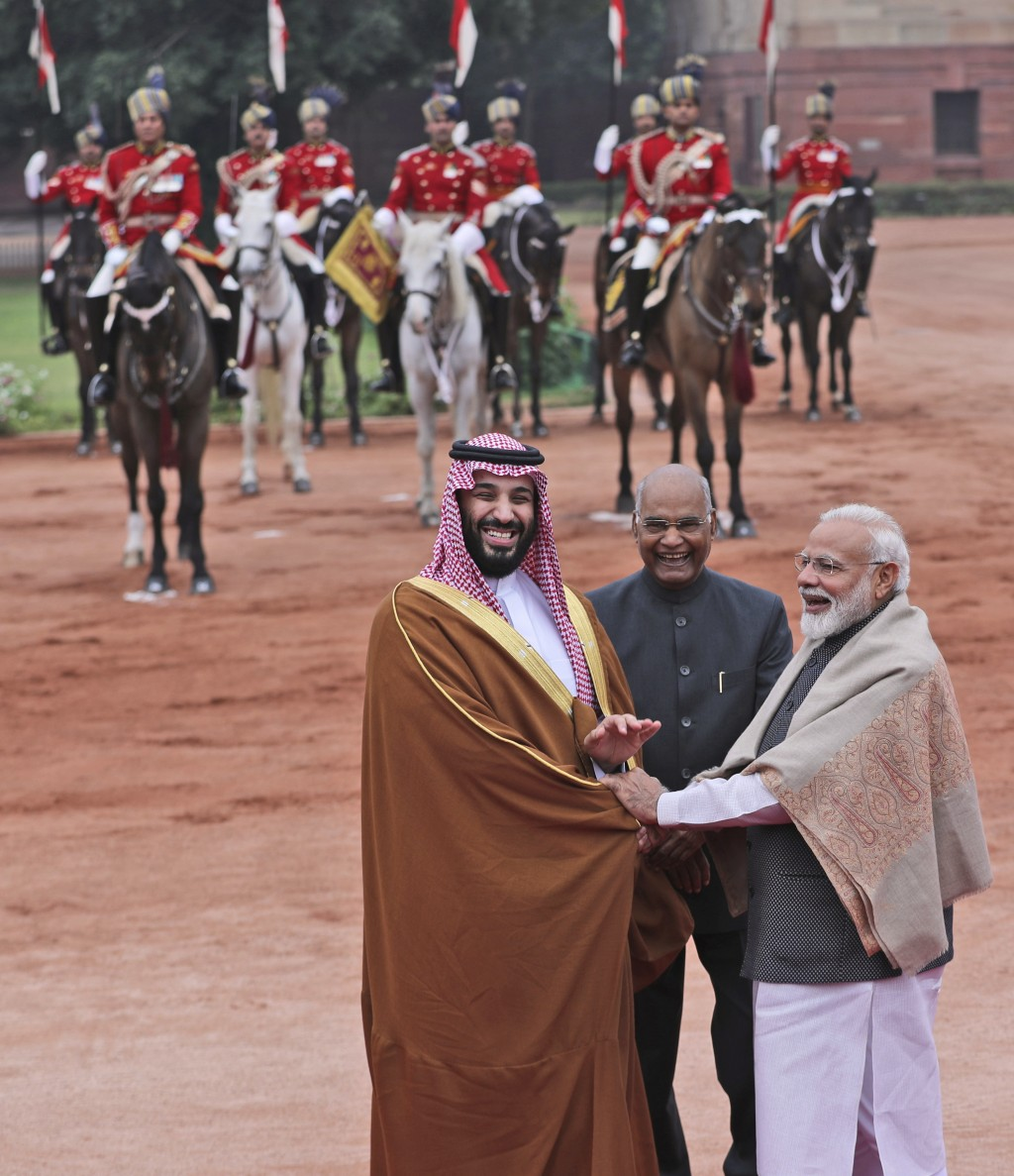 Saudi Arabia's Crown Prince Mohammed bin Salman shakes hand with Indian Prime Minister Narendra Modi, with Indian President Ram Nath Kovind standing b
