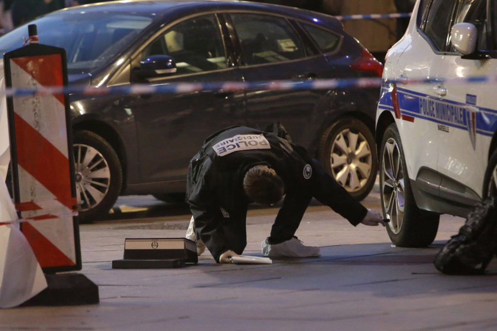 A police officer searches under a police car after an incident, in Marseille, southern France, Tuesday, Feb. 19, 2019. (AP Photo/Claude Paris)