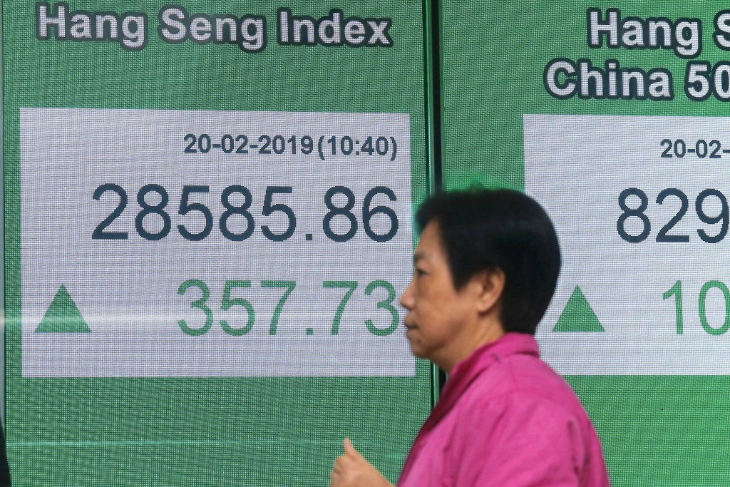 A woman walks past an electronic board showing Hong Kong share index outside a bank in Hong Kong, Wednesday, Feb. 20, 2019. Shares were mostly higher ...