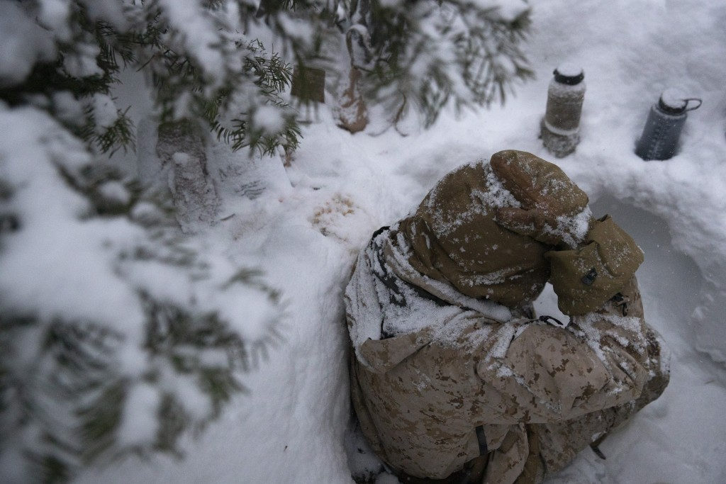 A U.S. Marine sits in a trench during advanced cold-weather training at the Marine Corps Mountain Warfare Training Center Saturday, Feb. 9, 2019, in B...