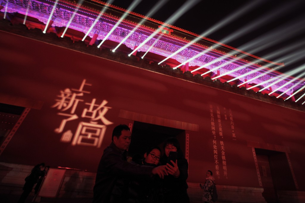In this Tuesday, Feb. 19, 2019, photo, a family take selfie with the Wumen Gate wall of the Forbidden City illuminated with lights for the Lantern Fes