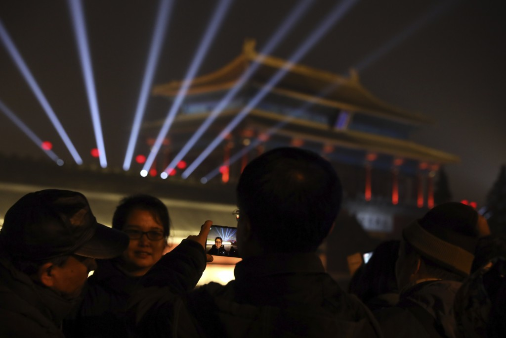 In this Feb. 19, 2019, photo, visitors take photos outside the Forbidden City to catch a glimpse of the evening lights in Beijing. China lit up the Fo