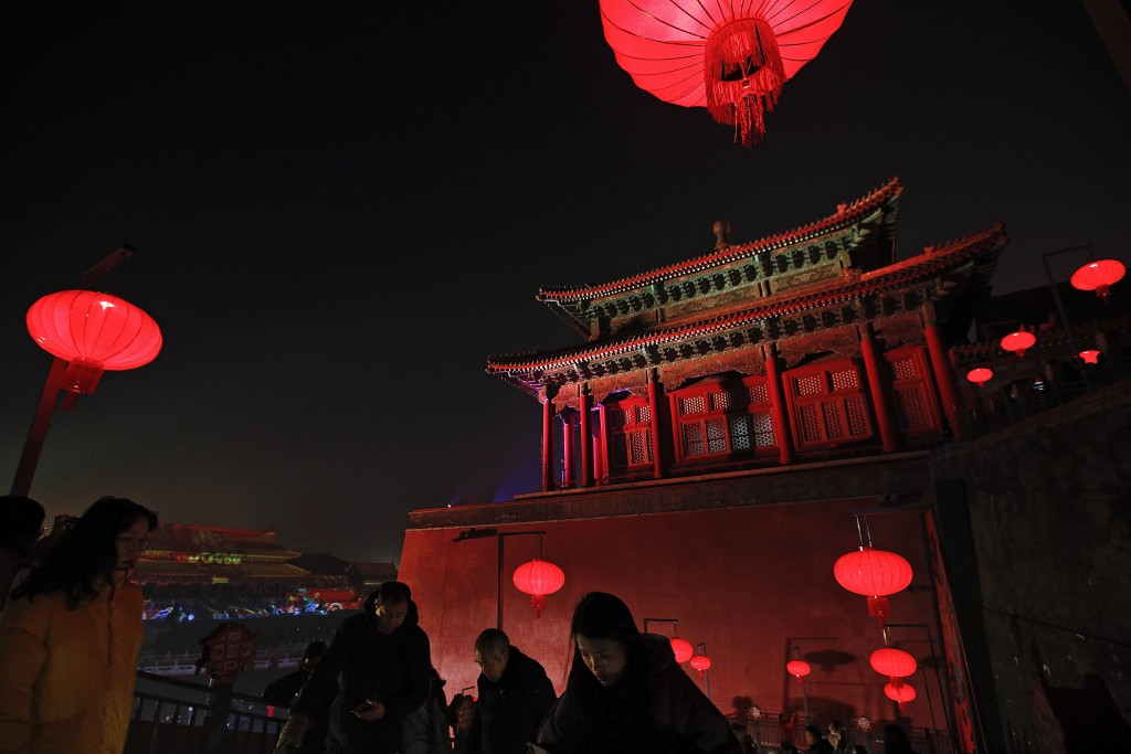 In this Tuesday, Feb. 19, 2019, photo, visitors tour the Forbidden City decorated with red lanterns and illuminated with lights for the Lantern Festiv