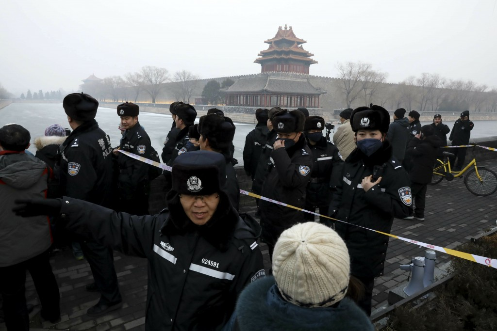In this Tuesday, Feb. 19, 2019, photo, Chinese police control a crowd gathered outside the Forbidden City to catch a glimpse of the evening lights in