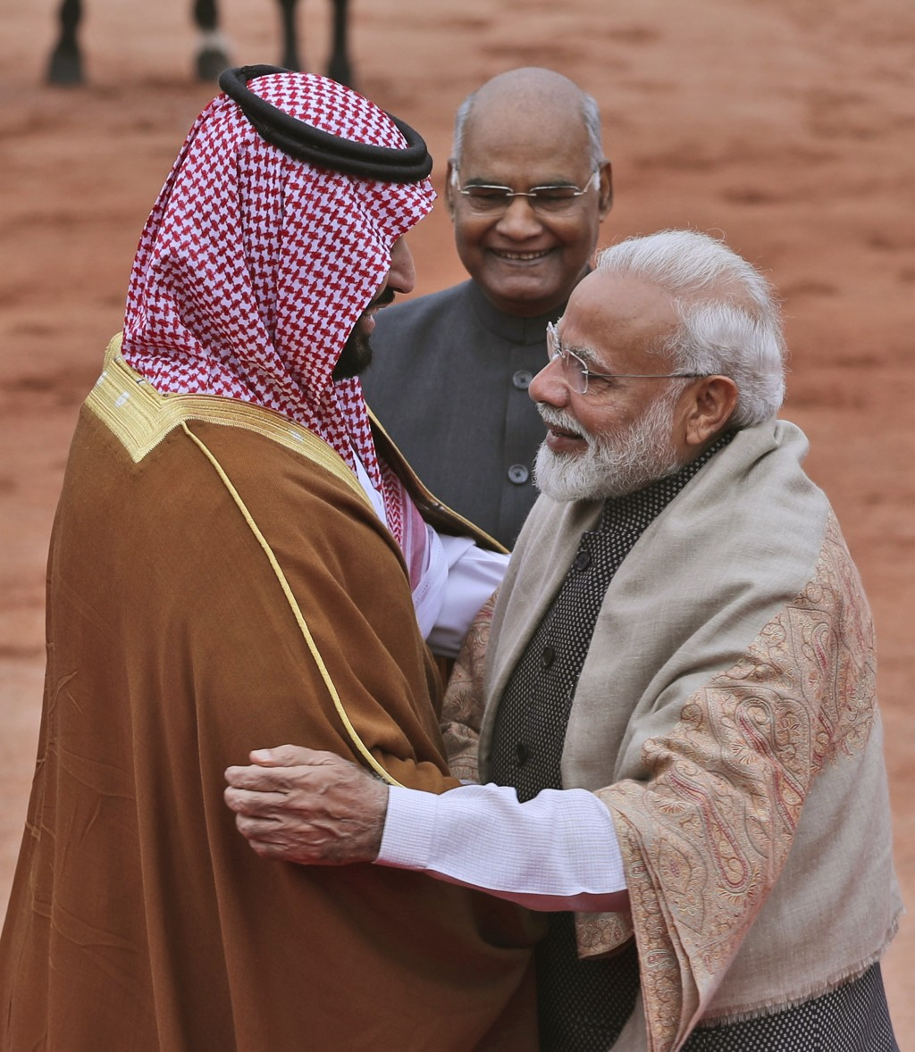 Indian Prime Minister Narendra Modi welcomes Saudi Arabia's Crown Prince Mohammed bin Salman with a hug, as Indian President Ram Nath Kovind stands be...