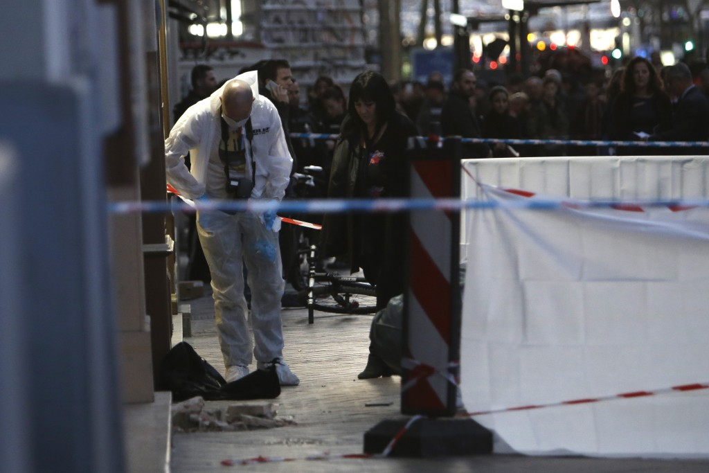Investigating police officers work at the scene after an incident, in Marseille, southern France, Tuesday, Feb. 19, 2019. (AP Photo/Claude Paris)