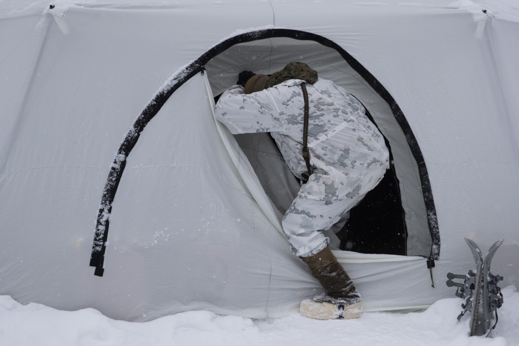 A U.S. Marine walks into a tent during advanced cold-weather training at the Marine Corps Mountain Warfare Training Center Saturday, Feb. 9, 2019, in ...