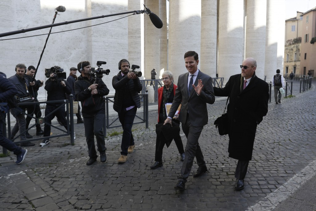 Juan Carlos Cruz, second from right, waves to journalists as walks to meet with organizers of the summit on preventing sexual abuse at the Vatican, We...