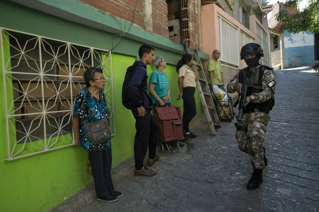 Residents stand near a wall as they watch a member of the National Police Action Force, or FAES, an elite commando unit created for anti-gang operatio