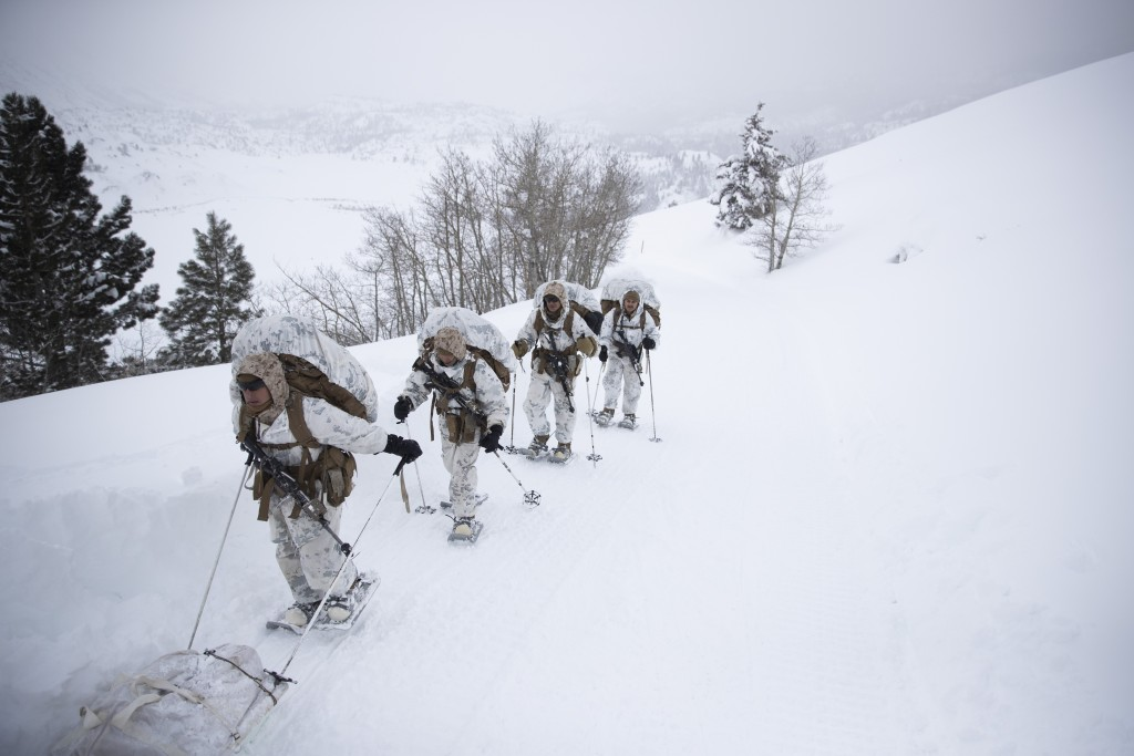 A group of U.S. Marines walk along a snow-covered trail during their advanced cold-weather training at the Marine Corps Mountain Warfare Training Cent...