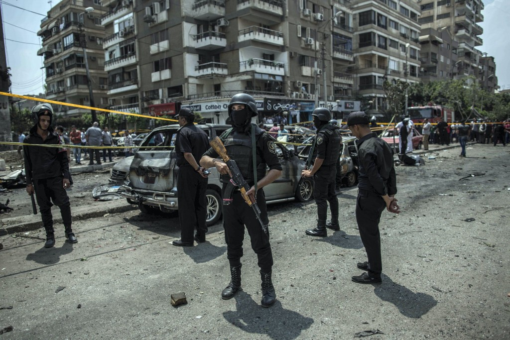 FILE -- In this June 29, 2015 file photo, Egyptian policemen stand guard at the site of a bombing that killed Egypt's top prosecutor, Hisham Barakat,