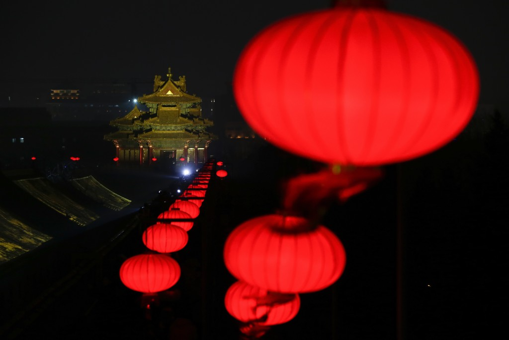 In this Tuesday, Feb. 19, 2019, photo, lanterns is decorated near a Turret of the Forbidden City projected with lights for the Lantern Festival in Bei