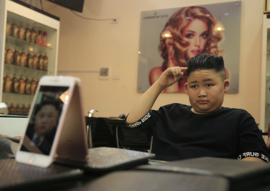 To Gia Huy, 9, checks his hair after having a Kim Jong Un haircut in Hanoi, Vietnam, on Tuesday, Feb. 19, 2019.  U.S. President Donald Trump and North