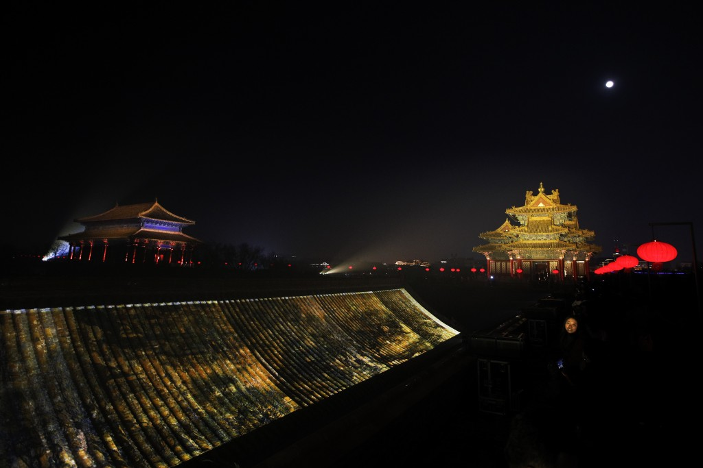 In this Tuesday, Feb. 19, 2019, photo, a woman's face is lit by lights as she visits to the Forbidden City decorated with lanterns and projected with
