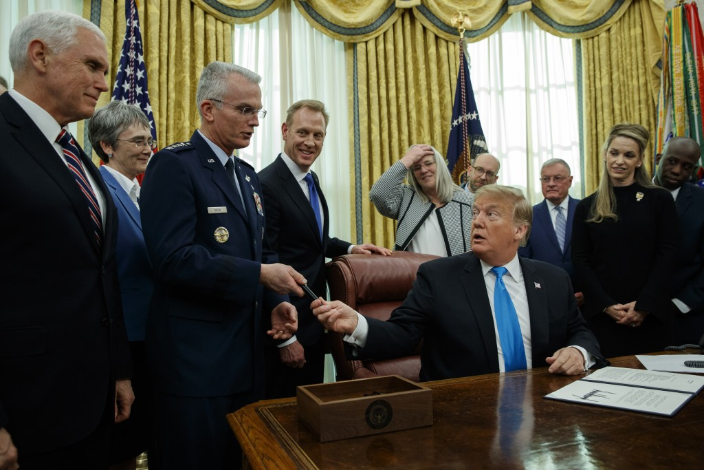 "President Donald Trump hands a pen to Air Force Gen. Paul Selva after signing ""Space Policy Directive 4"" in the Oval Office of the White House, Tuesda..."