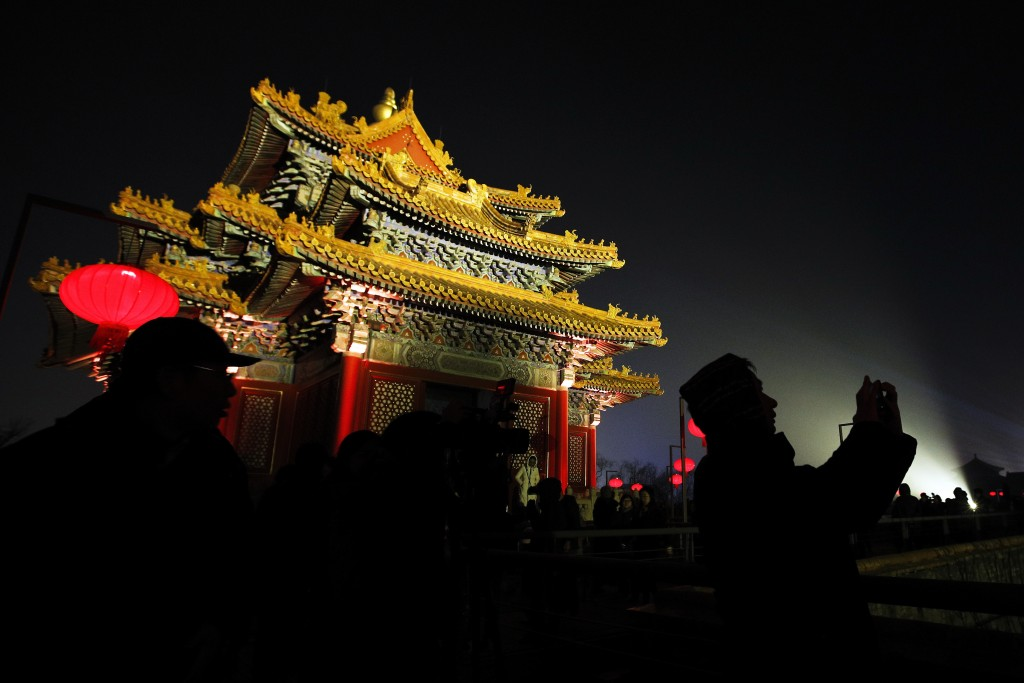 In this Tuesday, Feb. 19, 2019, photo, visitors is silhouetted as they tour the Forbidden City decorated with red lanterns and projected with lights f