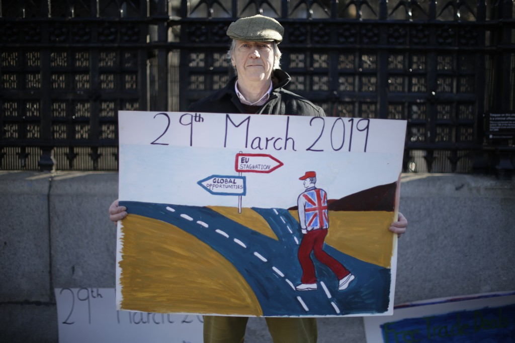 A leave the European Union supporter who didn't want to give his name poses for photographs outside the Houses of Parliament in London, Thursday, Feb.