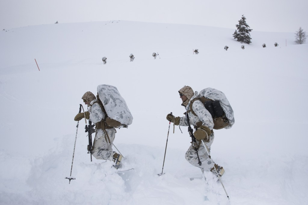 A group of U.S. Marines walk along a snow-covered trail during advanced cold-weather training at the Marine Corps Mountain Warfare Training Center Sun...