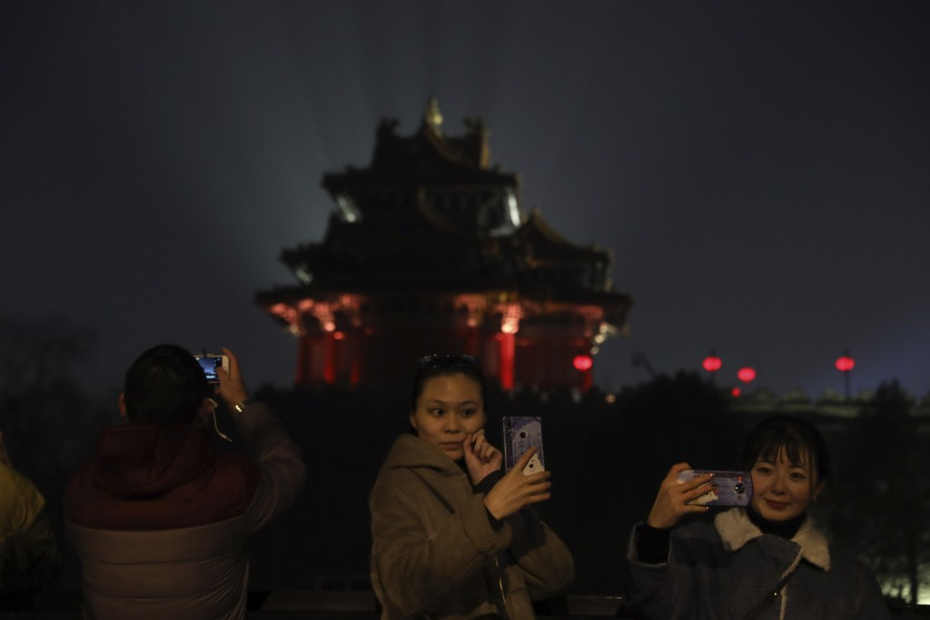 In this Feb. 19, 2019, photo, visitors pose for selfies outside the Forbidden City to catch a glimpse of the evening lights in Beijing. China lit up t