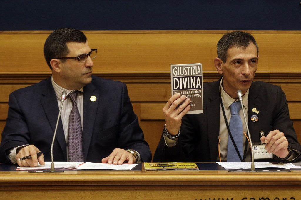 Survivor of sex abuse Francesco Zanardi, right, flanked by Mark Rozzi, Democratic member of the Pennsylvania House of Representatives, holds a book ti