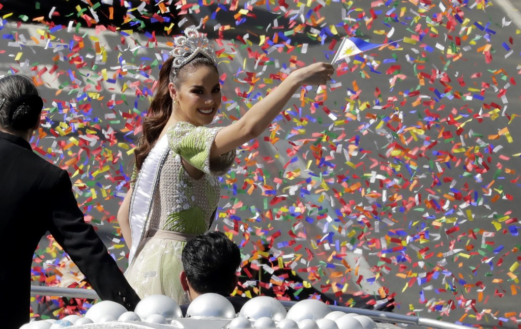 In this Thursday, Feb. 21, 2019, file photo, Confetti rains on new Miss Universe 2018 Catriona Gray as she waves a Philippine flag during her homecomi...