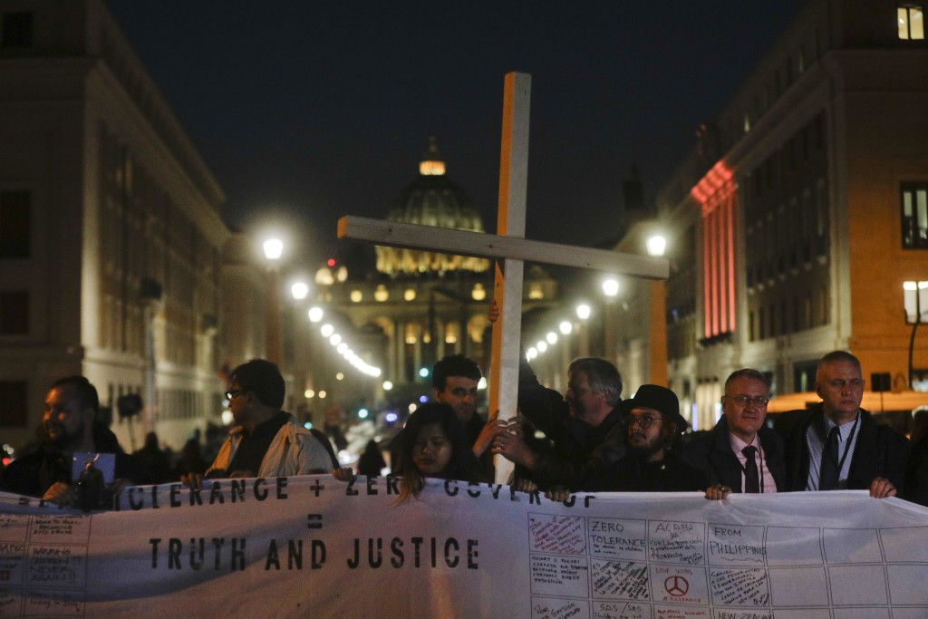Survivors of sex abuse hold a cross as they gather in front of Via della Conciliazione, the road leading to St. Peter's Square, visible in background,