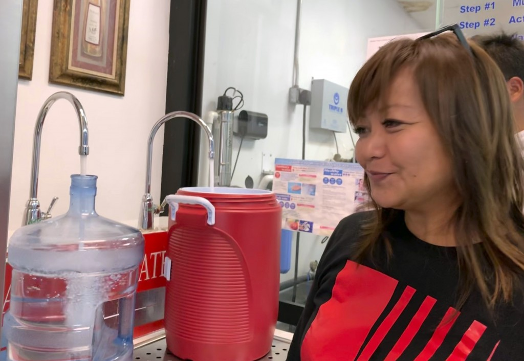 Vicky Borja, 53, fills her one of her two five-gallon jugs from a water filtration facility at a strip mall in Tamuning, Guam on Friday, Feb. 22. Typh...