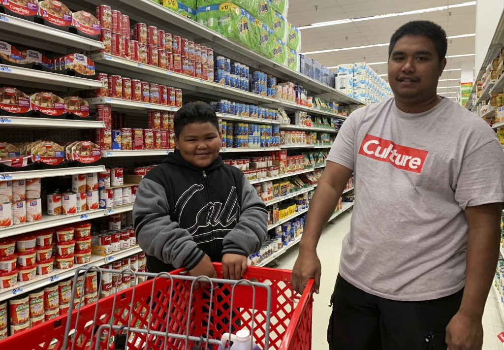 Tyrone Quinata, 23, and his nephew Rayden Gofigan, 11, shop for batteries and other necessities in Tamuning, Guam on Thursday, Feb. 21, 2019.  An inte