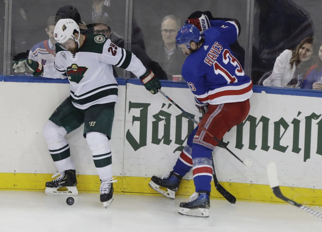 Minnesota Wild's Greg Pateryn (29) fights for control of the puck with New York Rangers' Kevin Hayes (13) during the third period of an NHL hockey gam