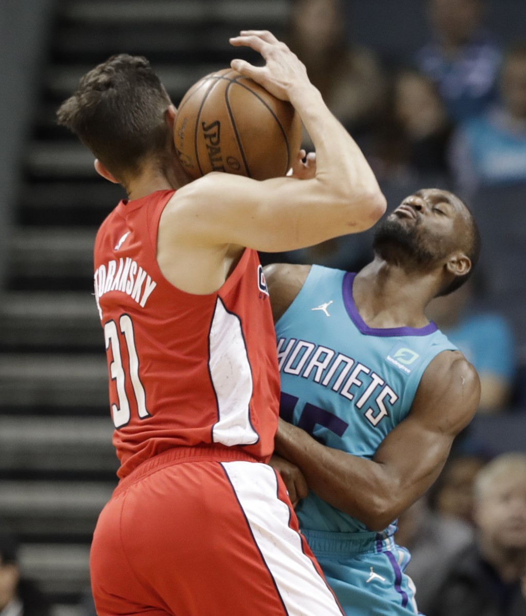 Washington Wizards guard Tomas Satoransky (31) runs into Charlotte Hornets guard Kemba Walker (15) during the first half of an NBA basketball game in ...