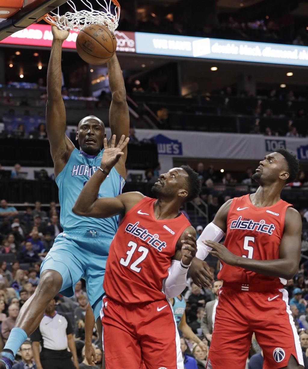 Charlotte Hornets center Bismack Biyombo, left, dunks against Washington Wizards forward Jeff Green (32) and Washington Wizards forward Bobby Portis (...