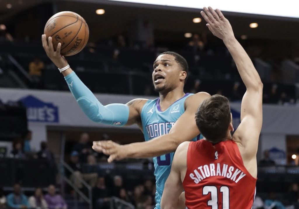 Charlotte Hornets forward Miles Bridges (0) drives against Washington Wizards guard Tomas Satoransky (31) during the first half of an NBA basketball g...