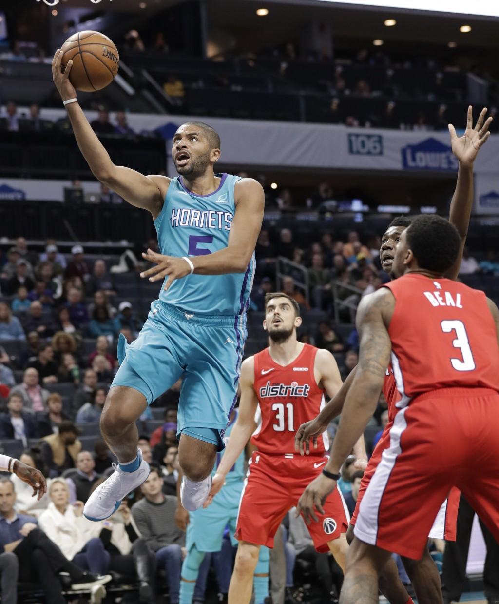 Charlotte Hornets forward Nicolas Batum (5) drives past Washington Wizards guard Bradley Beal (3) and Washington Wizards guard Tomas Satoransky (31) d...