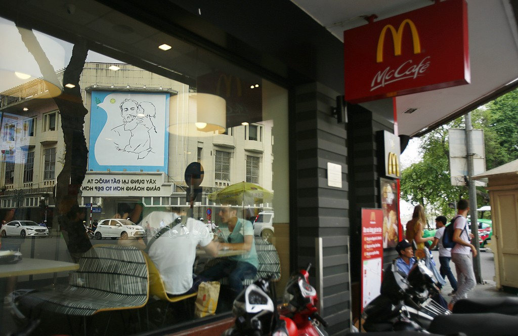 In this Feb. 21, 2019, photo, a poster of revolutionary leader Ho Chi Minh reflects on the glass window of a McDonald restaurant in Hanoi, Vietnam. Th...