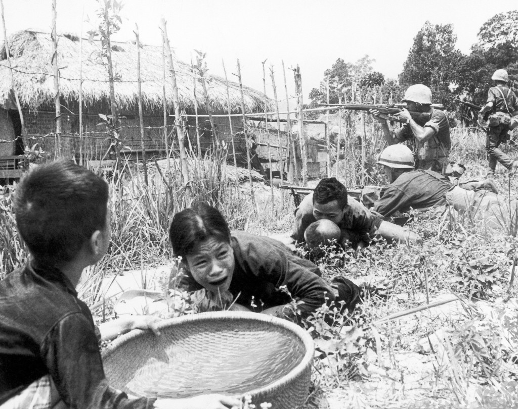 FILE - In this April 1965 under sniper fire, Vietnamese civilians duck for safety as U.S. Marines storm the village of My Son, near Da Nang in Vietnam...
