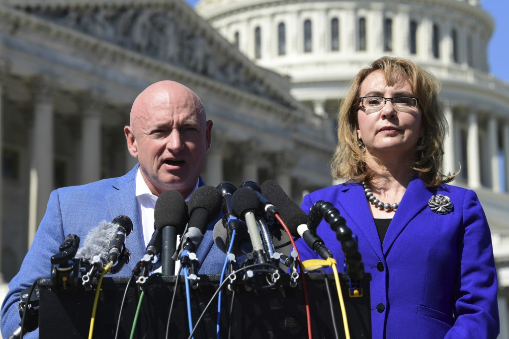 FILE- In this Oct. 2, 2017, file photo former Rep. Gabrielle Giffords, D-Ariz., right, listens as her husband Mark Kelly, left, speaks on Capitol Hill