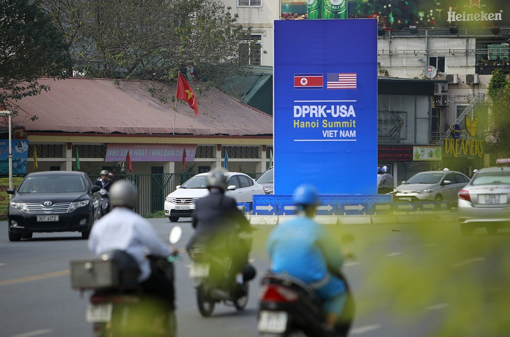 In this Feb. 21, 2019, photo, traffic passes a poster featuring the upcoming Trump-Kim summit in Hanoi, Vietnam. The Vietnamese capital once trembled