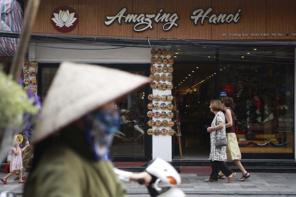 In this Feb. 21, 2019, photo, traffic passes a shop in Hanoi, Vietnam. The Vietnamese capital once trembled as waves of American bombers unleashed the...