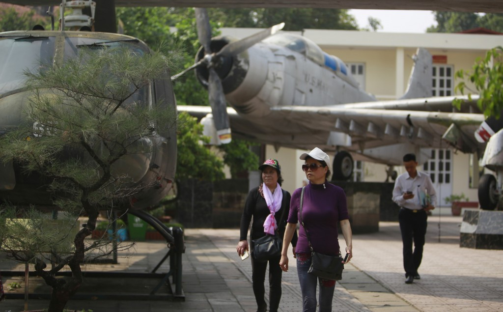 In this Feb. 21, 2019, photo, visitors walk next to American aircraft at the Vietnam Military History Museum in Hanoi, Vietnam. The Vietnamese capital