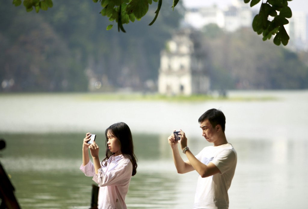 In this Feb. 21, 2019, photo, a couple take photos at the Hoan Kiem lake in Hanoi, Vietnam. The Vietnamese capital once trembled as waves of American