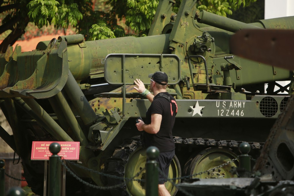 In this Feb. 21, 2019, photo, a visit touches bullet holes on an American artillery launcher at Vietnam Military History Museum in Hanoi, Vietnam. The