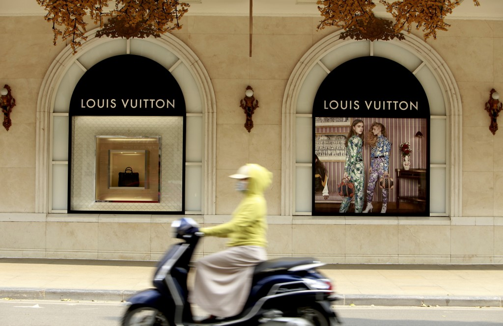 In this Feb. 21, 2019, photo, a motorcyclist passes a luxury shopping mall in Hanoi, Vietnam. The Vietnamese capital once trembled as waves of America