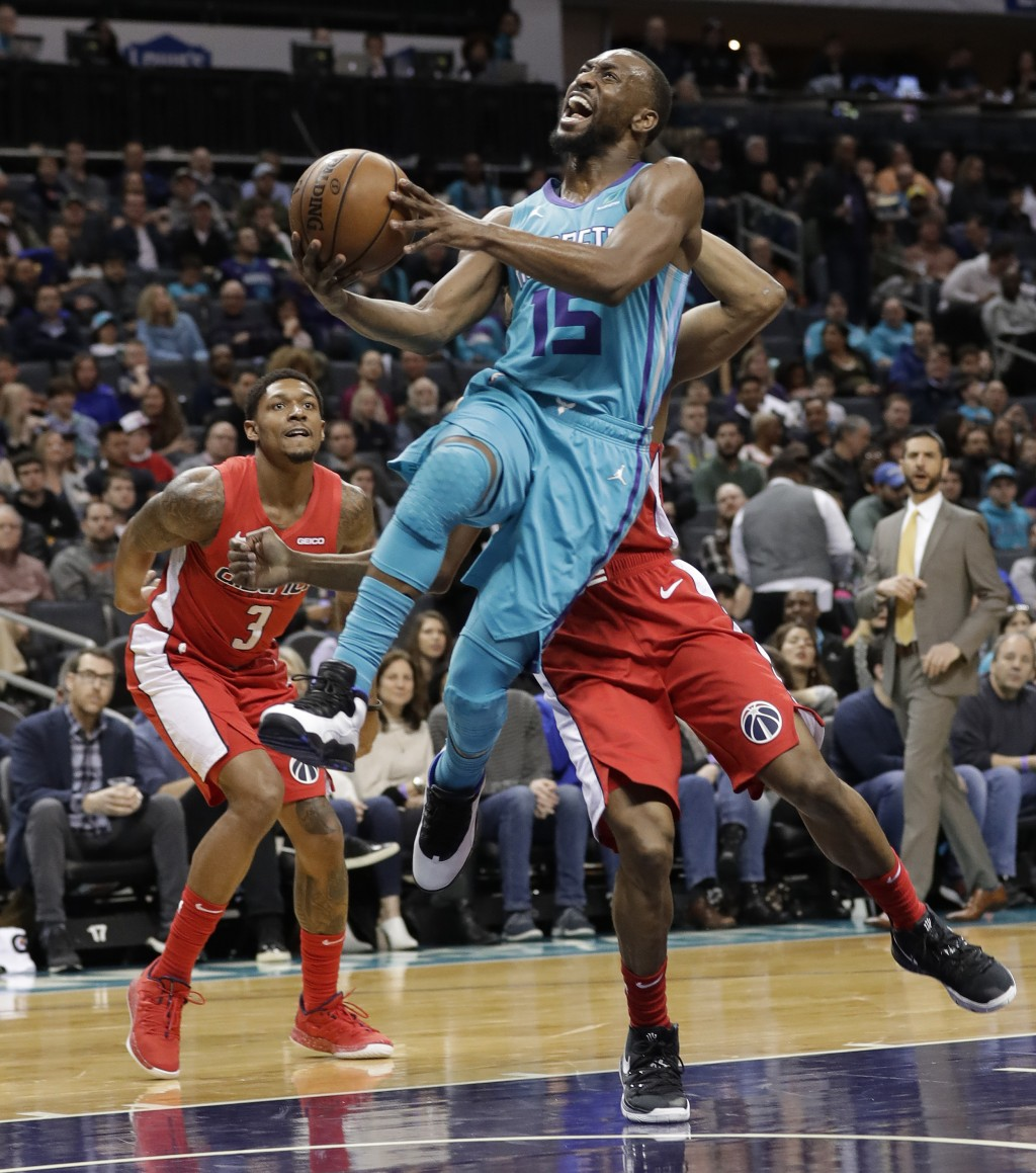 Charlotte Hornets guard Kemba Walker (15) drives past Washington Wizards guard Bradley Beal (3) during the first half of an NBA basketball game in Cha...