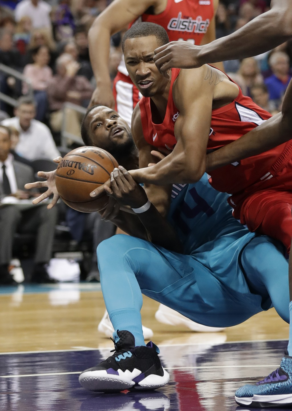 Charlotte Hornets forward Michael Kidd-Gilchrist, left, and Washington Wizards forward Wesley Johnson, right, battle for the ball during the first hal...