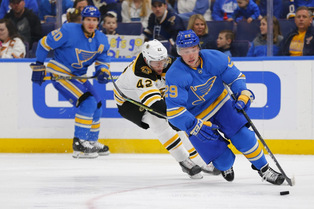 St. Louis Blues' Vince Dunn (29) controls the puck against Boston Bruins' David Backes (42) during the first period of an NHL hockey game Saturday, Fe